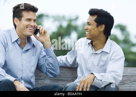 Two men sitting on bench, smiling, one using cell phone - Stock Photo