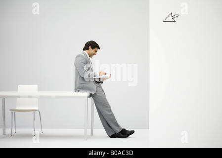 Businessman leaning against desk, using laptop computer, cursor graphic in foreground - Stock Photo