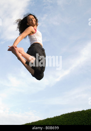 A young woman girl jumping on a trampoline, UK - Stockfoto