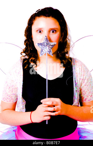 Young girl dressed in fairy outfit with star shaped wand held in front of face eyes looking surprised - Stockfoto