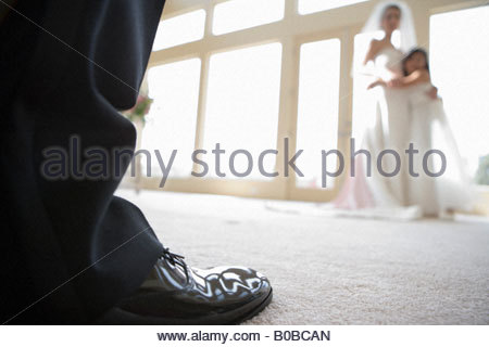 Bride and bridesmaid  embracing beside window, focus on groom's shoe in foreground, close-up surface level - Stock Photo