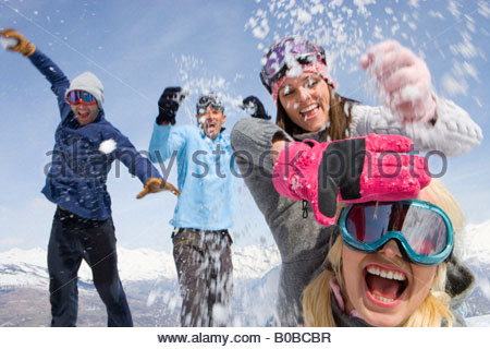 Two young couples having snow fight in snow field, mountain range in background - Stockfoto