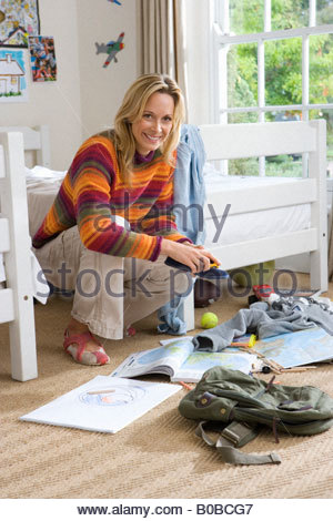Woman tidying child's bedroom, smiling, portrait - Stock Photo