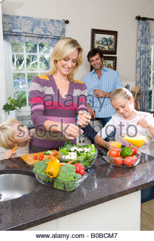 Mother making salad by daughter  pouring juice, father in background - Stock Photo