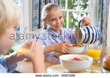 Brother and sister  at breakfast table, girl pouring milk, smiling, portrait differential focus - Stock Photo