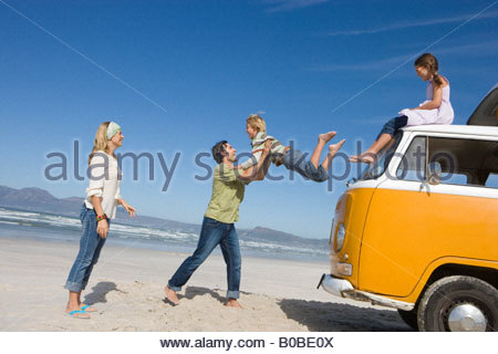 Family of four on beach, father catching son  jump from roof of camper van, side view - Stock Photo
