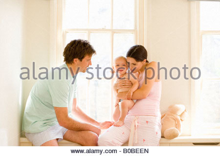 Young couple in pajamas on windowsill, mother holding baby girl 6-9 months, portrait of baby - Stock Photo
