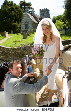 Groom helping bride into vintage car, church in background, smiling, portrait - Stock Photo