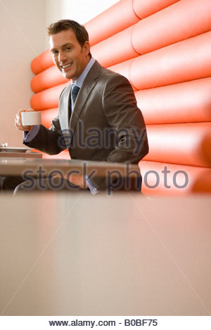 Businessman with cup at table in booth, smiling, portrait, low angle view - Stockfoto