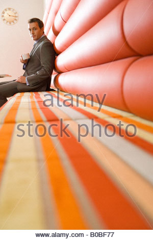 Businessman with mug sitting beneath clock on wall in booth, portrait, low angle view - Stockfoto