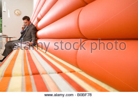 Businessman in booth using mobile phone, reading paperwork under clock on wall, - Stockfoto