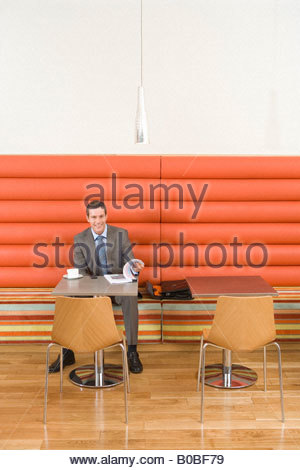 Businessman in booth at table with coffee cup and paperwork, smiling, portrait - Stockfoto