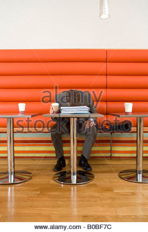 Businessman at table in cafe, disposable cup in hand, head on paperwork - Stockfoto