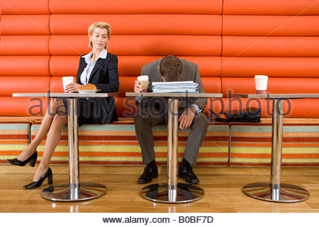 Businesswoman at table in cafe looking at businessman with head collapsed on paperwork, disposable cup in hand - Stockfoto