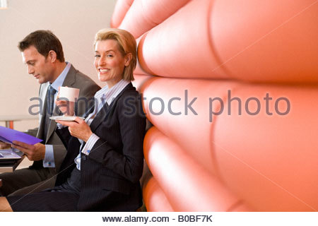Businessman and woman having meeting in booth in cafe, woman with coffee cup, smiling, portrait - Stockfoto