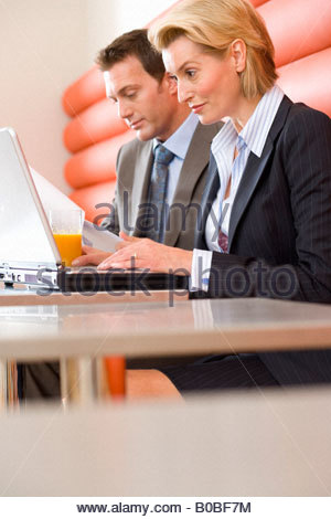 Businessman and woman having meeting in cafe, woman using laptop computer, low angle view - Stockfoto