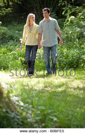 Young couple hand in hand in forest, low angle view - Stock Photo