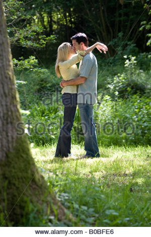 Young couple embracing in forest, side view - Stock Photo