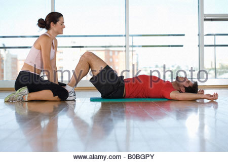Woman helping man with sit-ups in gym studio, side view - Stock Photo