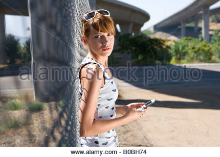 Young woman with mobile phone by fence, smiling, portrait, side view - Stock Photo