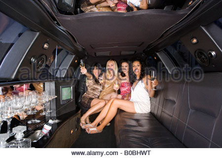Medium group of young women with drinks in limousine, reflection in ceiling, smiling, portrait - Stock Photo