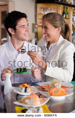 Young couple smiling at each other in Japanese restaurant, woman with chopsticks - Stock Photo