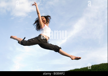 A teenage girl jumping on a trampoline - Stockfoto
