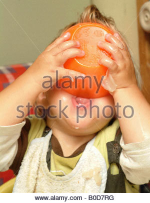 Baby eating food inside child little boy holding hungry funny humor humour fun BABIES BABYS Toddler infant toddlers - Stock Photo
