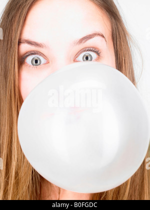 Woman blowing up a bubble gum - Stock Photo