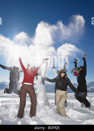 Group throwing snowballs in air - Stockfoto