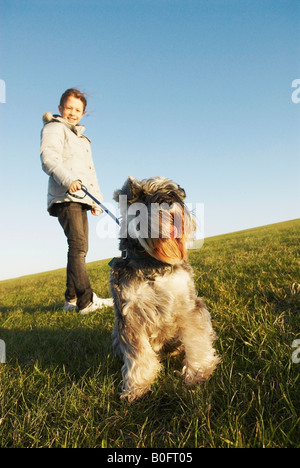 Girl holds dog on lead on hill - Stock Photo