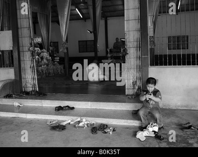 little boy outside tewmple playing on mobile, inside young man being ordained, bangkok, thailand - Stock Photo