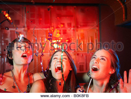 Three women in a nightclub drinking and laughing - Stock Photo