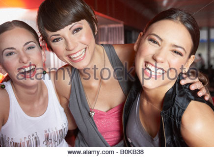 Three women in nightclub having fun and smiling - Stock Photo
