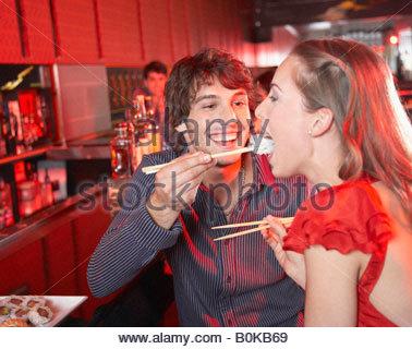 Man feeding woman sushi in nightclub and smiling - Stockfoto