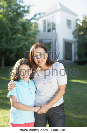 Woman and young girl standing outdoors holding hands and smiling - Stockfoto
