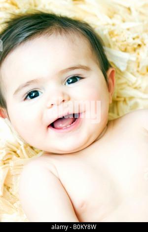 Baby lying down on yellow shag rug laughing - Stockfoto