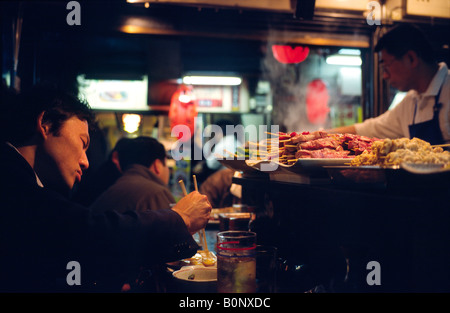 Man eating at one of the dimly lit Izakayas serving Yakitori in Shinjuku's Golden Gai area in the Japanese capital - Stockfoto