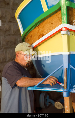 Maltese Man repainting a LuzzuA Traditional Maltese foreign fishing boats - Stockfoto