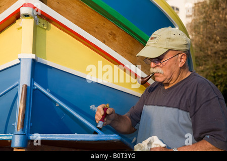 Man repainting a LuzzuA Traditional Maltese foreign fishing boats - Stockfoto