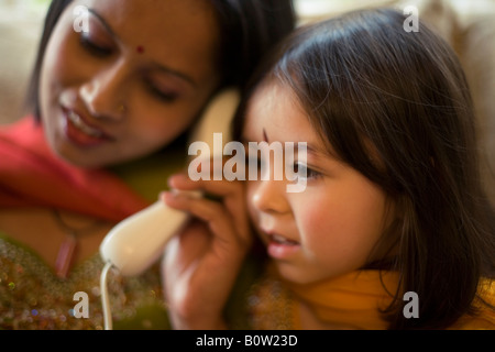 Pakistani mother and mixed race daughter in traditional dress telephone home - Stock Photo