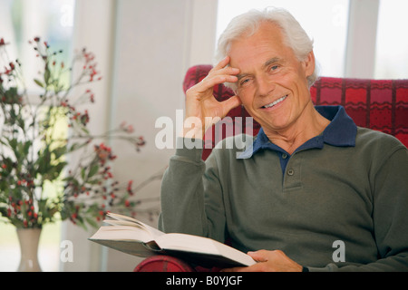 Senior man with book, relaxing, portrait - Stock Photo