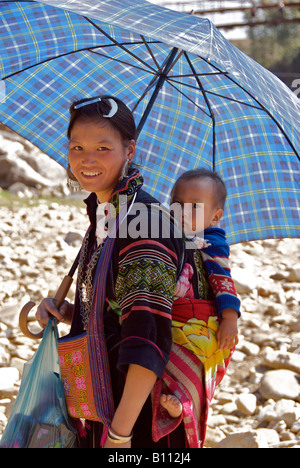 Black Hmong woman carrying baby and umbrella near Sapa Northern Vietnam - Stock Photo