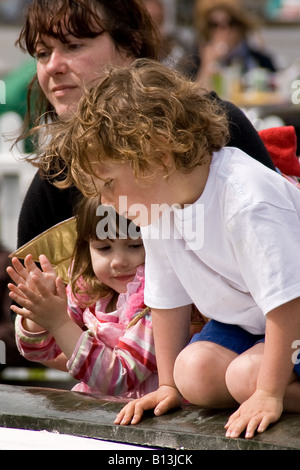 two toddlers kneeling by a fountain - Stockfoto