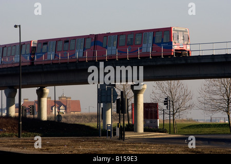 One of the trains of the Docklands Light Railway London over a bridge in the Docklands - Stock Photo