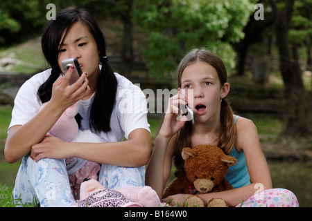 Stock Photograph of two girls talking on cell phones - Stock Photo