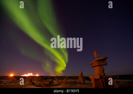 Northern Lights, Aurora borealis, above an inukshuk in the town of Churchill with the lights of the Port of Churchill - Stock Photo
