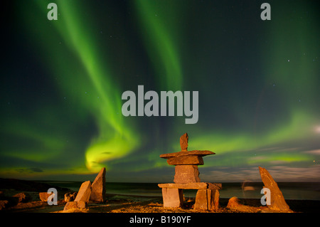 Northern Lights, Aurora borealis, above an inukshuk in the town of Churchill, Hudson Bay, Manitoba, Canada. - Stock Photo
