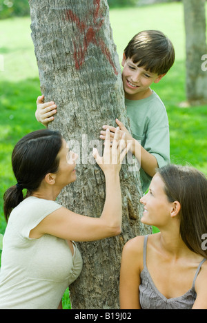Mother and son embracing tree, teen daughter smiling over shoulder at them - Stock Photo
