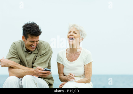 Senior woman and adult son sitting side by side outdoors, laughing, man holding cell phone - Stock Photo